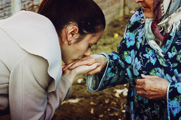 Granddaughter kisses old hands of his grandmother