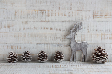 Weihnachten - Holzintergrund mit Rentier und Tannenzapfen