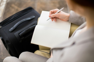 High angle close up of unrecognizable young businesswoman writing in notebook while waiting for business travel with suitcases