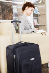Side view portrait of elegant young businesswoman in hotel lobby waiting and making notes sitting on sofa with suitcases