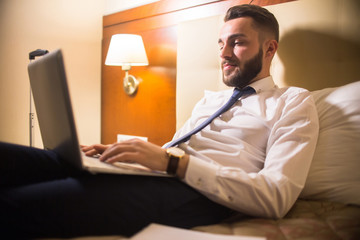 Portrait of handsome bearded businessman using laptop in bed enjoying hotel stay during business travel