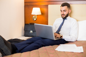 Full length portrait of handsome bearded businessman using laptop in bed enjoying hotel stay during business trip