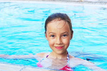 Cute little girl is smiling in swimming pool. Summer, vacation, sport concept