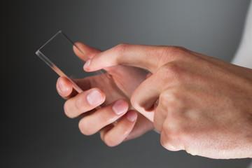 Hands holding futuristic transparent phone