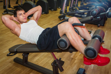Young  man trains the abdominal muscles