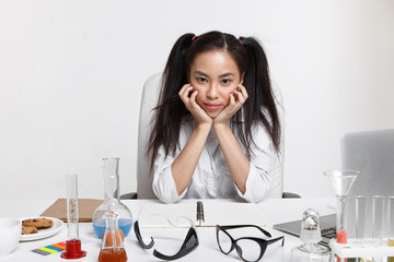 Picture of tired young brunette Japanese female chemist assistant wearing white uniform working in laboratory, sitting at workplace with many test tubes, flasks, goggles and laptop computer on desk