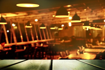 black top of table with blur row of lamp light in restaurant or bar at night background