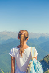 Happy woman traveler in the mountains and the landscape of mountains and blue sky Travel lifestyle concept of adventure summer holidays.