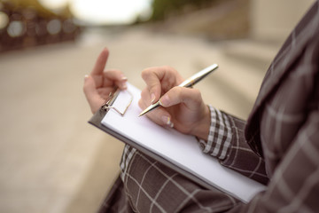 Horizontal shot of female hands close-up writing in notebook. Photo tonted orange