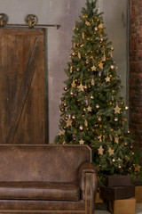Beautiful Christmas interior with decorated holiday tree and brown leather sofa. Dark loft interior.