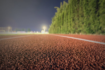 Running track close up. Night time shallow depth of field. Sport Background.