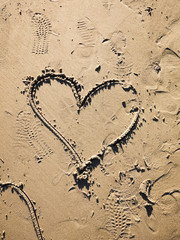 Hand-drawn heart symbol in the wet, golden sand at a beach in California and footprints