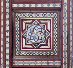 Closeup of arabesque seamless pattern on an ancient old wooden tea table