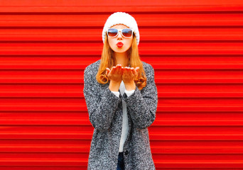 Fashion young woman blowing red lips sends an air kiss on a background