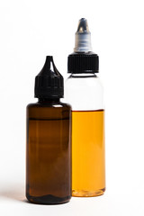 e- liquid, e-juice in the bottles isolated on the white background with copyspace
