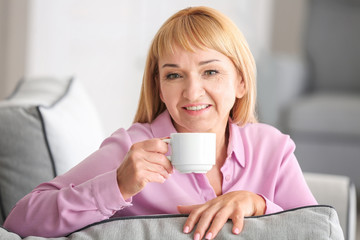 Beautiful mature woman drinking coffee while  sitting on sofa at home