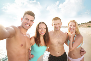Group of young people taking selfie on beach
