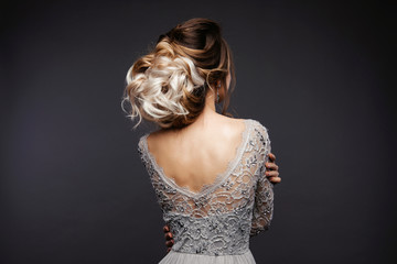 Studio Portrait of a Beautiful Bride Model in a Light Gray Wedding Dress with Elegant  Hairstyle and Pink Lips at Gray Background