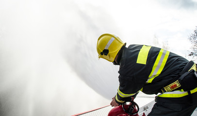Firefighters with a hose in action