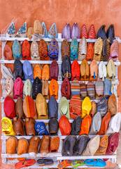 A range of colorful moroccan leather shoes displayed at street shop bazaar. Oriental style design. Travel destination concept. Colorful background.
