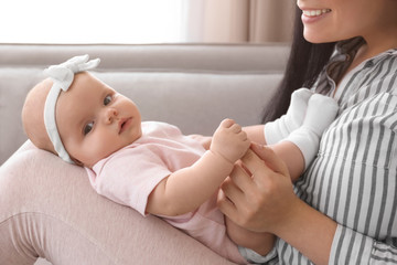 Cute baby holding mother's finger at home