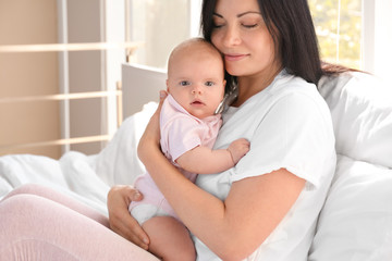 Young mother with baby on bed at home