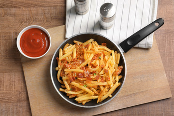 Frying pan with french fries and bacon on table
