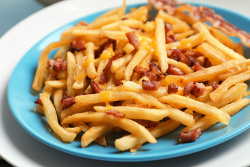 Plate with french fries and bacon on table, closeup