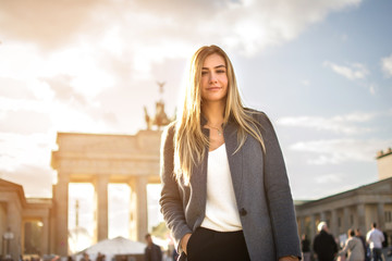 Portrait of smiling fashionable young woman in front of Brandenburger Tor in Berlin, Germany.