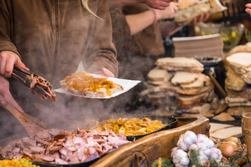 Food booth selling traditional Polish street food in Main Square, Kraków at Christmas market.
