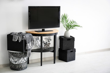 Modern TV on stand against light wall background