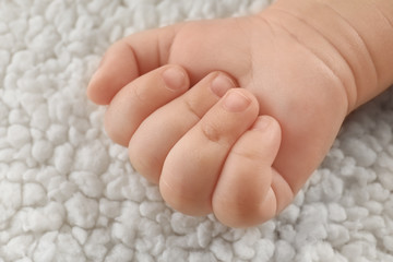 Baby hand on light plaid, closeup