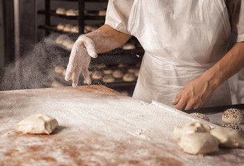 Man preparing buns in bakery