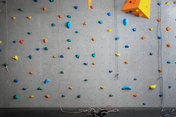 Grey wall with climbing holds and ropes in gym