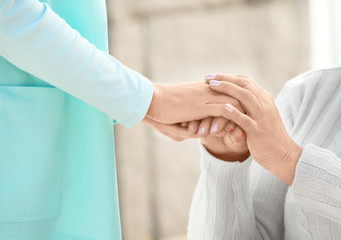 Senior woman and young caregiver holding hands, closeup