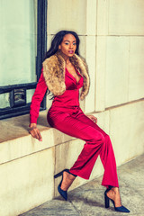 African American Woman Fashion in New York, dressing in red slim fashionable jacket, pants, black high heel pumps shoes, faux fur scarf on shoulder, sits on frame of window outside. Filtered effect..
