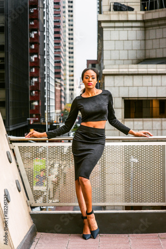 becc9d76e1e African American Business Woman Fashion in New York. Lady wearing black  long sleeve crop top, skit, high heel pumps shoes, stands by railing on  balcony.
