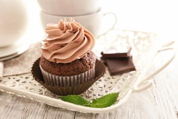 Tasty chocolate cupcake on tray