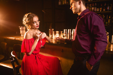 Woman in dress flirts with man behind bar counter