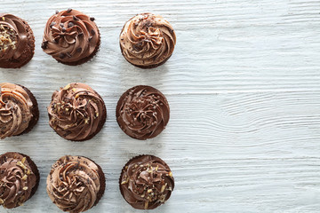 Tasty chocolate cupcakes on wooden background