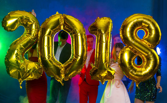 The composition of the golden balloons in the form of figures on a background of a dancing group of young people. The new year 2018. Festive New Year party or disco.