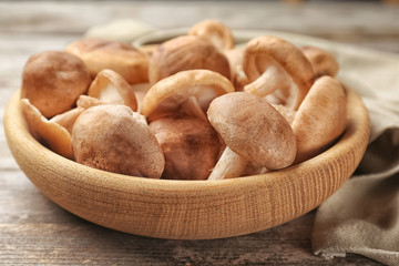 Bowl with raw shiitake mushrooms on wooden table, closeup
