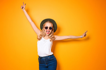 Attractive hipster girl with hat and sunglasses on color background