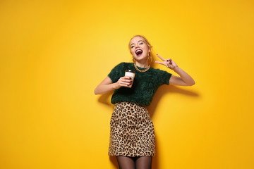 Attractive hipster girl with cup of coffee on color background