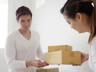 Happy couple smiling, packing and closing carton box for send to customer,owner business sme concept