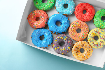 Tasty glazed donuts in box on color background