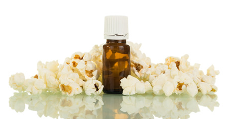 Bottle with liquid for inhalation of vapour from electronic cigarettes, near lot of popcorn, isolated on white