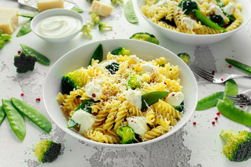 Pasta with green vegetables broccoli, Mange tout and creamy sauce in white plate
