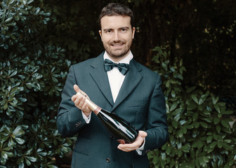 Portrait of waiter holding a bottle of champagne