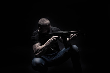 portrait of a handsome male bodybuilder, on a black background isolated, with an automatic weapon, an assault rifle in his hands. The concept of a photo of sport,